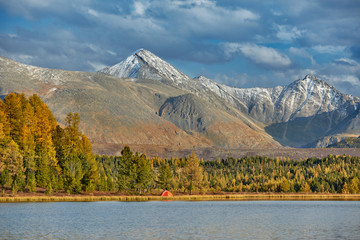 First snow on Lake. Colorful autumn landscape.