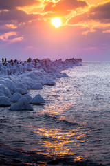 A beautiful evening landscape of a frozen breakwater in the Baltic sea. Winter landscape at the beach. Vivid colors.