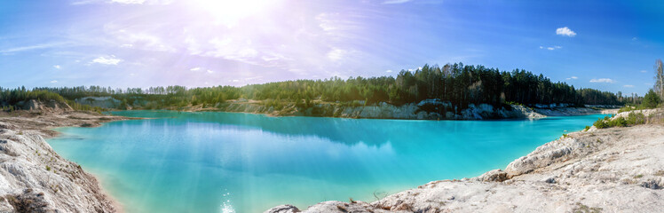 Panorama of a scenic flooded clay quarry with turquoise water in the morning sun