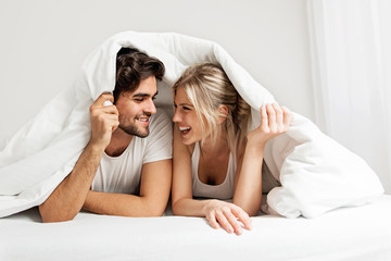 Young loving couple lying on the bed, enjoying