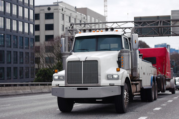 Towing powerful semi truck tow broken big rig semi truck fleet on the city street traffic