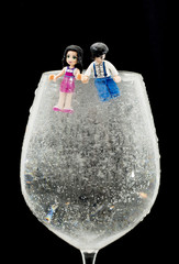 Two lego figures in a wine glass filled up with water