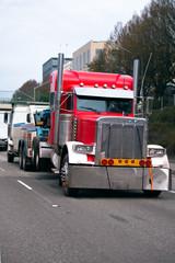 Towing semi truck tow broken big rig semi truck on the city street traffic