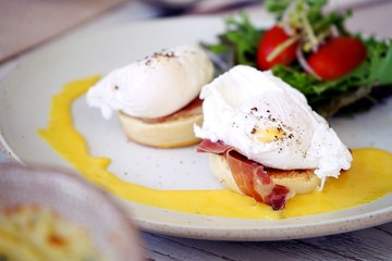breakfast is egg benedict,consist of eggs, english muffin, canadian bacon and Hollandaise sauce served with salad placed on white dish.