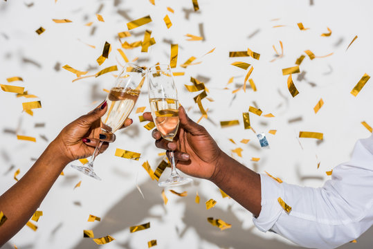 close-up partial view of african american couple clinking glasses of champagne on white with golden confetti