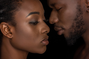 side view of young african american couple with water drops on faces posing isolated on black
