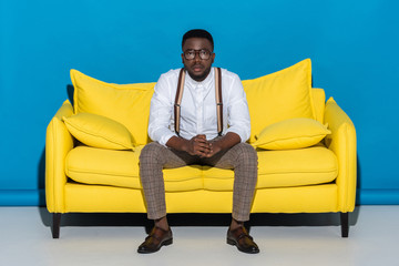 young african american man in eyeglasses sitting on sofa and looking at camera