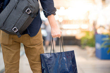 Closeup of male hand holding blue shopping bag in department store. Urban lifestyle in shopping mall concept