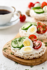 Open sandwiches of rice cakes with cream cheese , vegetables and quail egg