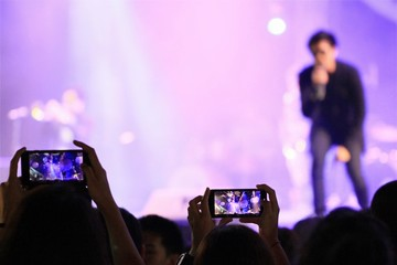 People holding their smart phones and photographing concert in front of the stage of music concert festival