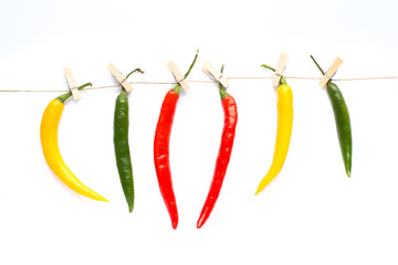 colorful peppers pinned with paperclips, hang, dries, background with colorful paprika