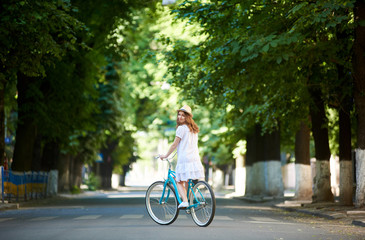 Green urban plantings. Female rides on retro bike alone at road on a summer day. The girl is dressed in a light dress and hat on her head