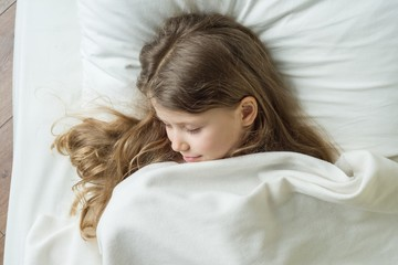 Girl child 7 years old blonde with long wavy hair sleeping on a pillow in bed