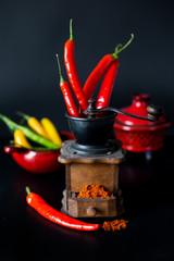 ground red pepper, grinder and paprikar on a black background