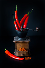 ground red pepper, grinder and paprikar on a black background