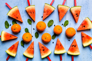 summer concept watermelon slice popsicles on a blue rustic wood background