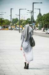 Veiled Muslim woman walking in the street near the train station