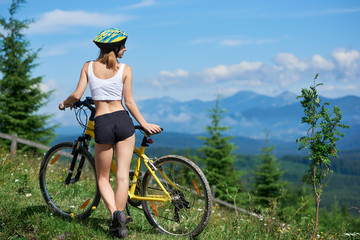 Rear view young attracive female athlete standing on a rural trail with yellow bicycle, wearing helmet, enjoying valley view and foggy mountains on the background in the morning. Copy space
