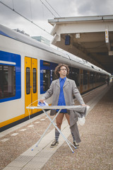 Man ironing his suit in the city on the platform of a railway train station
