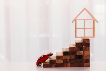 Toy car driving up towards the stairs of achievement with house on the top - big dream and growth achievement in buying house and property.