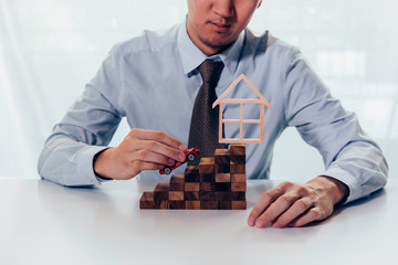 Conceptual of businessman taking a toy car driving up towards the stairs of achievement with house on the top - big dream and growth achievement in buying house and property.