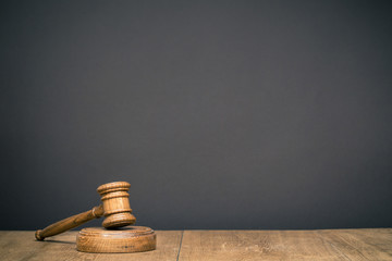 Retro auction or judge wooden gavel in front black wall background. Symbol of justice. Vintage old style filtered photo