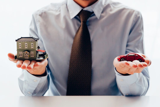 Conceptual of businessman in dilemma of planning to choose between spending either house or car first - buying real estate and car decision making concept.