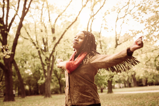 African American young woman dancing in park alone.