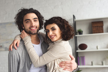 smiling girlfriend hugging boyfriend and they looking at camera at home