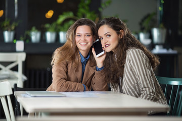 Girlfriends listening phone conversation in cafe and smiling