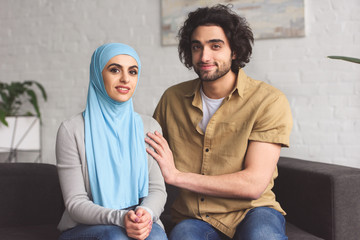 muslim couple sitting on sofa and looking at camera at home