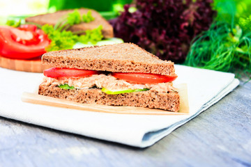 Food for breakfast, lunch, snack, picnic. Sandwich with rye bread slices, ripe tomatoes, fresh cucumbers, canned tuna fish on a napkin on a wooden table, selective focus. Healthy and organic food.