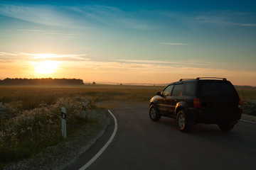 Beautiful Landscape With  Black Car On Asphalt Road Under Blue Sky With Sunset Of Sun In Early Dawn Summer.