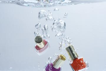Nail polish fall into pure, transparent water.