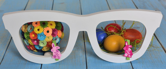 Happy Easter. A white decorative glasses through which can be seen painted colorful Easter eggs and a ball with  paper colorful flowers. flowers from paper technique quilling