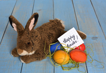 Happy Easter. A funny toy bunny and a few painted Easter eggs on blue wooden  background. on the sheet of paper  the wish is written - Happy Easter