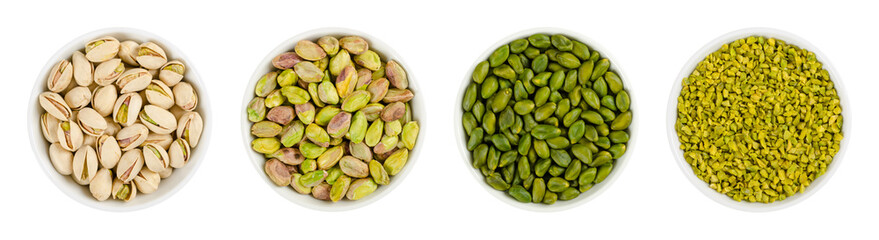 Pistachios in white porcelain bowls. Roasted pistachio seeds in shells and shelled. Green, dried fruits, whole and chopped. Pistacia vera. Isolated food photo close up from above on white background.