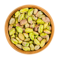 Shelled, roasted pistachios in wooden bowl. Green seeds and ripe fruits of Pistacia vera, used as snack. Isolated macro food photo close up from above on white background.
