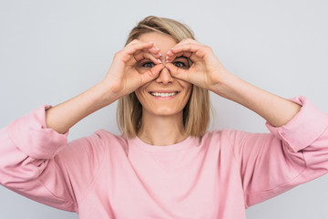 Portrait of beautiful blonde female wearing pink casual sweater holding her hands at her eyes as if looking through binoculars or glasses. Surprised happy woman against studio white wall background Wall mural
