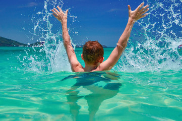 Child splashing in sea. Boy (10 years old) hands up in turquoise water tropical sea. Seascape with bright sky and sea. Back view.