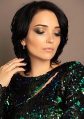 beautiful woman with dark hair and evening makeup posing in studio