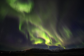 Aurora in dark sky over snow mountain