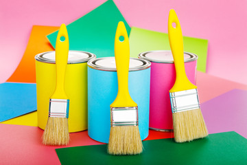 Cans of paint and paintbrush on colorful background. Pastel color