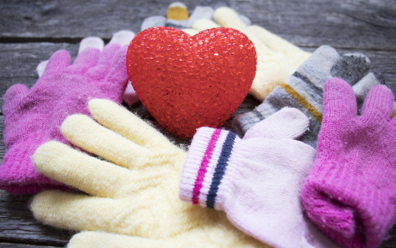 heart and knitted baby gloves on wooden background