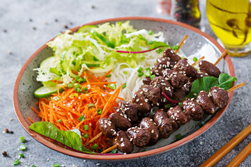 Chicken hearts in spicy sauce, noodles and vegetable salad. Healthy food.