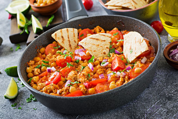 Chili con carne of turkey  with chickpeas served with nachos.  Chili with meat, nachos, lime, hot pepper. Mexican / Texas traditional food.