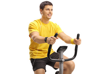 Young guy with headphones exercising on a stationary bike