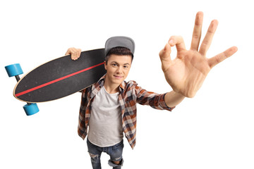 Teenage skater with a longboard making an OK gesture