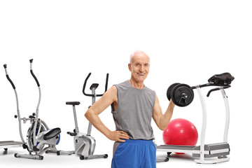 Elderly man with a dumbbell in front of exercise machines