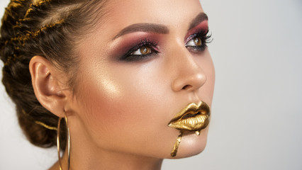 side view of face of young girl with the shining smooth healthy skin of person brightly by the distinctly painted eyes and gold on lips